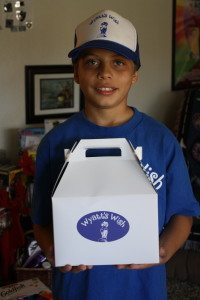 Wyatt, decked out in Wyatt's Wish gear, holding a completed care package.