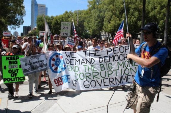 """Marchers say, """"We the people demand Democracy. End the Big Money corruption of government."""" Photo by Dan Bacher."""