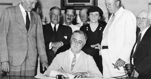 President Roosevelt signs the Social Security Act, at approximately 3:30 pm EDT on August 14, 1935. Standing with Roosevelt are Rep. Robert Doughton (D-NC); unknown person in shadow; Sen. Robert Wagner (D-NY); Rep. John Dingell (D-MI); Rep. Joshua Twing Brooks (D-Pennsylvania); the Secretary of Labor, Frances Perkins; Sen. Pat Harrison (D-MS); and Rep. David Lewis (D-MD). (Photo: Archive/Wikimedia Commons)