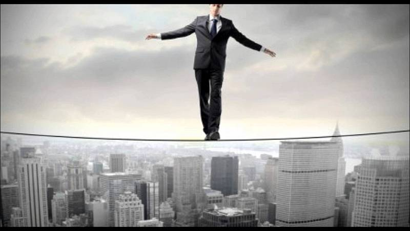 Man in suit balancing on tightrope over skyline of skyscrapers