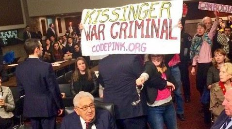 "Code Pink activists with ""Kissinger War Criminal"" banner behind seated Kissinger"