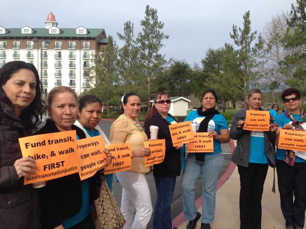 Environmental Health Coalition members hold signs outside SANDAG board meeting