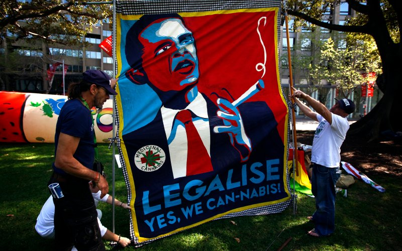 Three people setting up a banner reading: Legalise - Yes We Cannabis!