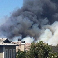 San Diego houses with smoke from 2014 fires rising behind them