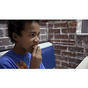 Child taking a bite of food in a restaurant booth