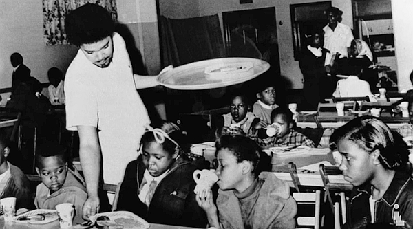 Member of the Black Panther Party serving breakfast to young black children