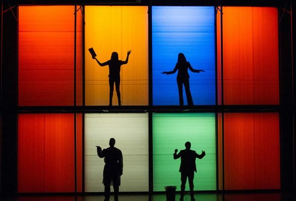 "Stage scene from ""Smart People"": four actors sillhouetted in boxes back-lit in varied colors"