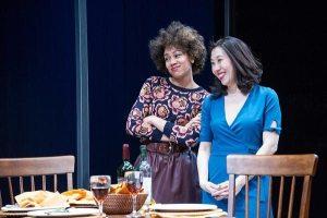 Two women standing near table set for dinner