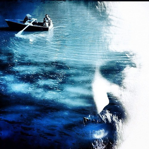 Blue monochromatic image of three people in rowboat on calm water with man's face subtly appearing in the surface of the water