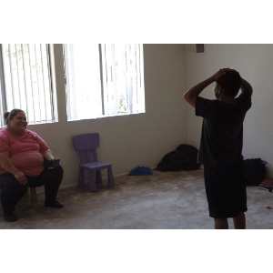 Seated woman and standing preteen in unfurnished apartment room