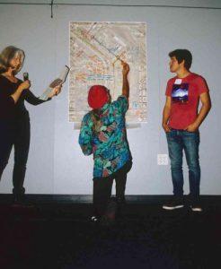 Three people examining urban planning map on wall
