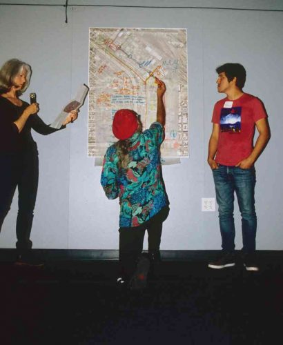 Three people examining urban planning map on wall
