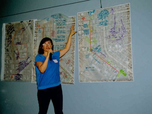 Woman standing in front of three urban planning maps on wall