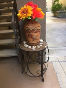Large red and yellow flowers in Mexican style ceramic vase in patio courtyard