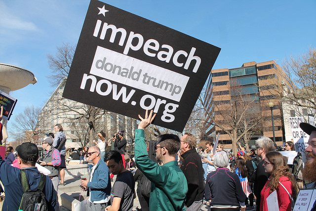 "Crowd with person holding sign: ""impeach donald trump now .org"