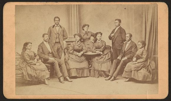 Members of the Jubilee Singers, nine men and women sitting or standing before the camera.
