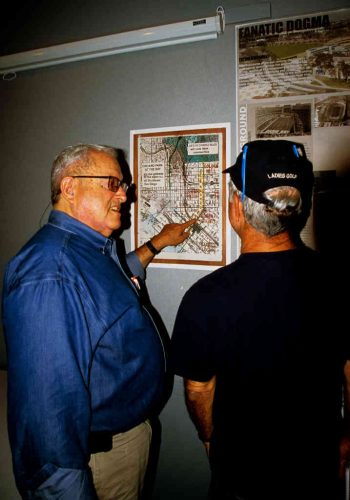 Two men examine urban planning map on wall