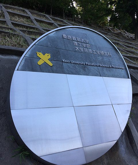 Sign for Keio University displaying crossed pen nibs symbol