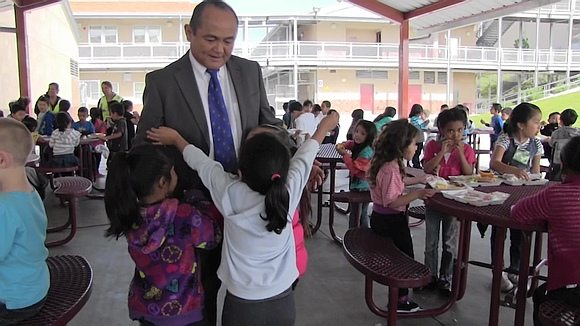 Principal Higa with young children in school cafeteria