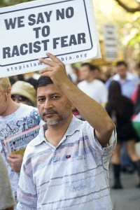 """Man holding sign: """"WE SAY NO TO RACIST FEAR"""""""