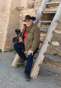 Isaac Artenstein sitting on wooden ladder propped against Pueblo style building
