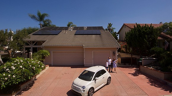 House with solar panels on roof, electric car, man, woman and two children in driveway