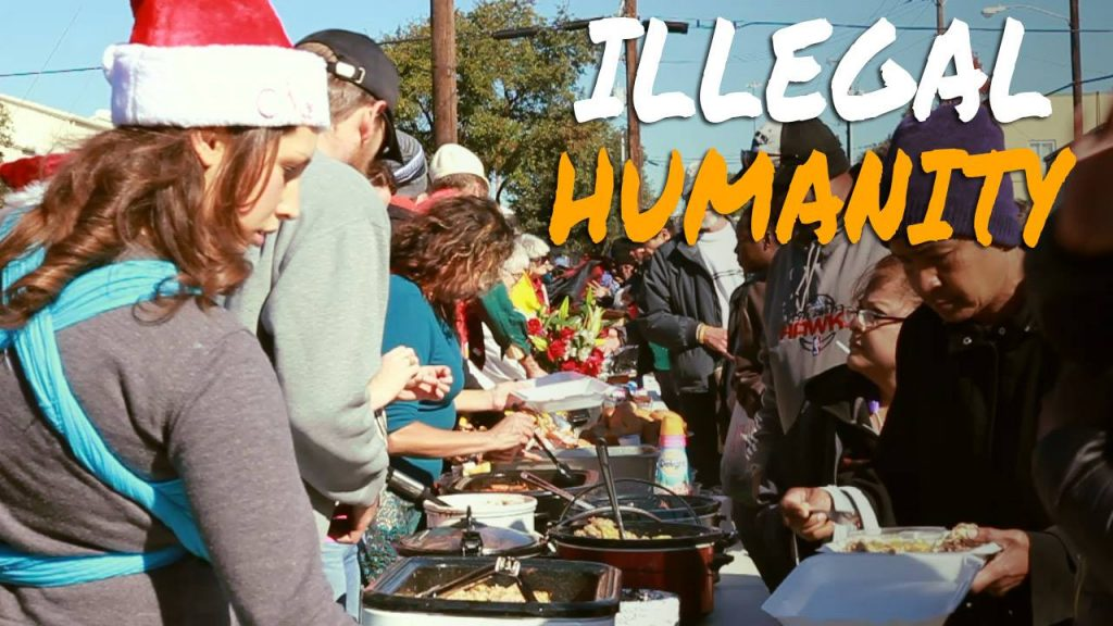 "Text: ""ILLEGAL HUMANITY"" superimposed on photo of people being served food at outdoor event."