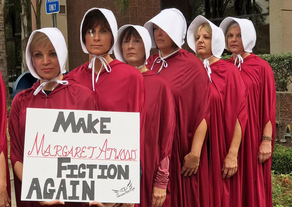 "Women dressed as characters from ""The Handmaid's Tale"" holding sign ""Make Margaret Atwood Fiction Again"""