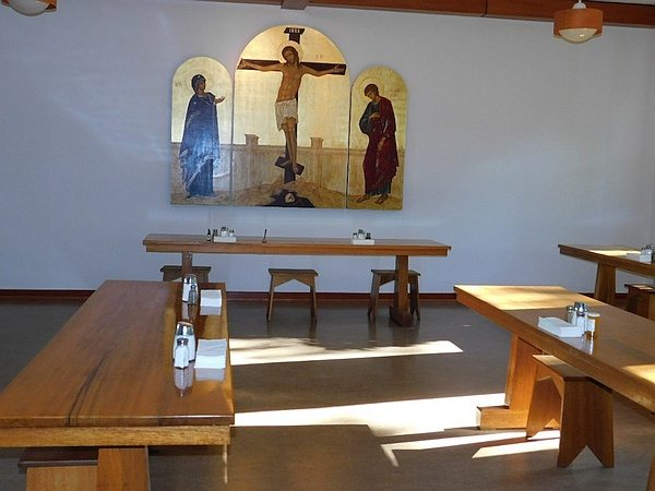 Dining area with wooden tables and crucifixion triptych