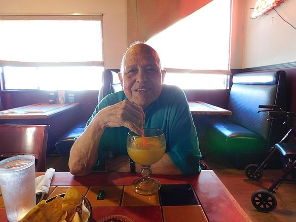 Smiling man seated at diner table with goblet of orange juice