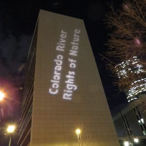 """Side of Denver, Colorado Federal Building with projected sign reading """"Colorado River Rights of Nature"""""""