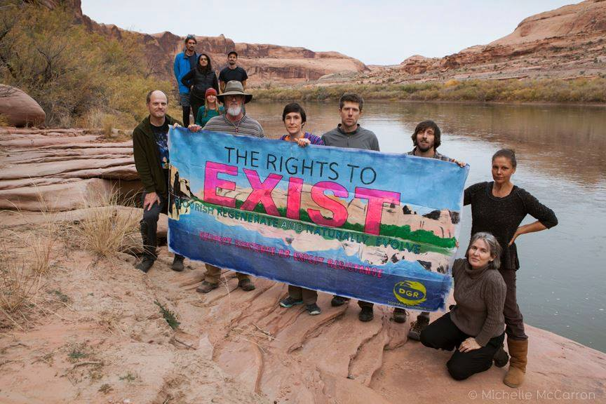 """Group on river bank holding banner reading """"THE RIGHT TO EXIST"""""""
