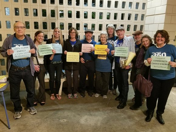 Group of SD350 volunteers standing in semicircle holding signs in support of Community Choice Energy