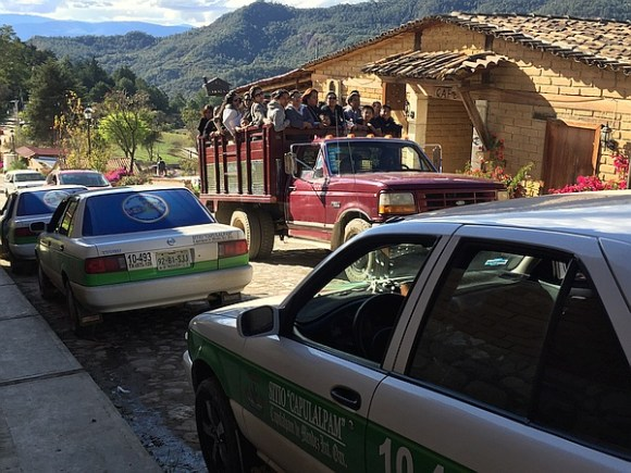Street scene in Oaxaca with taxis and a truck carrying people