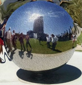 Metallic orb reflecting people walking in Fault Line Pak