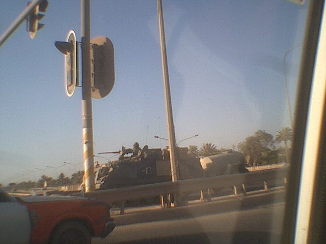 View through car window from inside, of military vehicle on city street