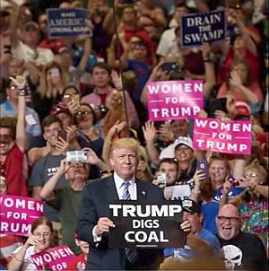 """Donald Trump at rally holding sign """"TRUMP DIGS COAL"""""""