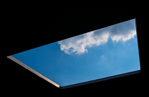 View of blue sky and cloud through a square hole in black ceiling
