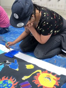 Kneeling teen painting a mural laid out on the ground
