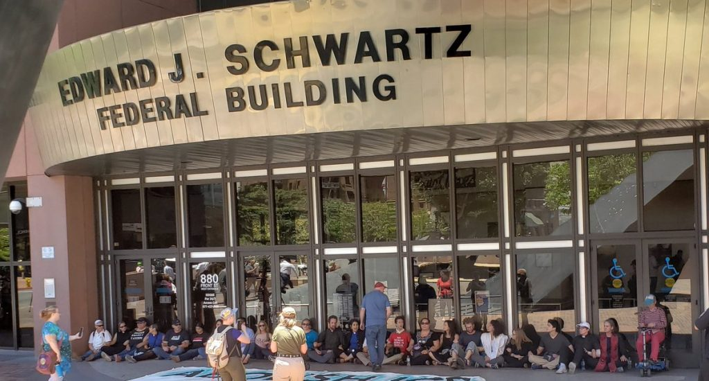 Seated protesters with arms linked blocking entrance to Edward J. Schwartz Federal Building