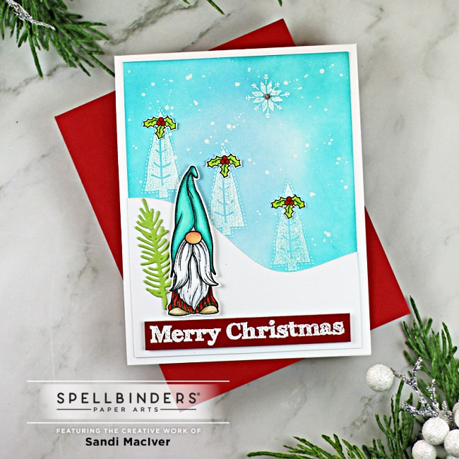 handmade christmas card in blue and red with a little gnome and snowy trees created with the Holiday Gnomes stamp set from Spellbinders
