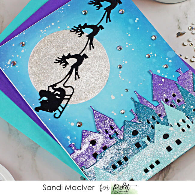 handmade christmas card with a village and santa and reindeer up iin the sky, cardmaking supplies from Picket Fence Studios