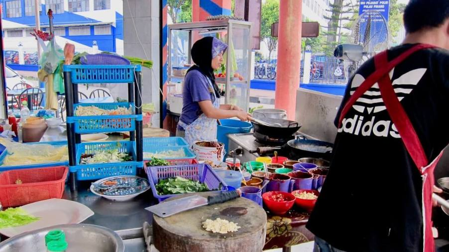 Malay woman in tudong cooking in wok