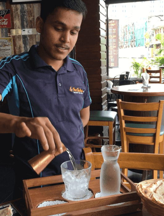 Server pouring a drink at Olive-where to eat in penang