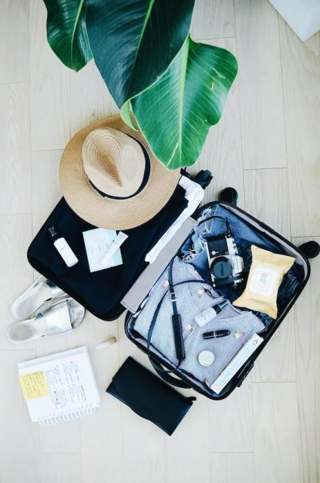 packed suitcase with hats and camera: moving to malaysia
