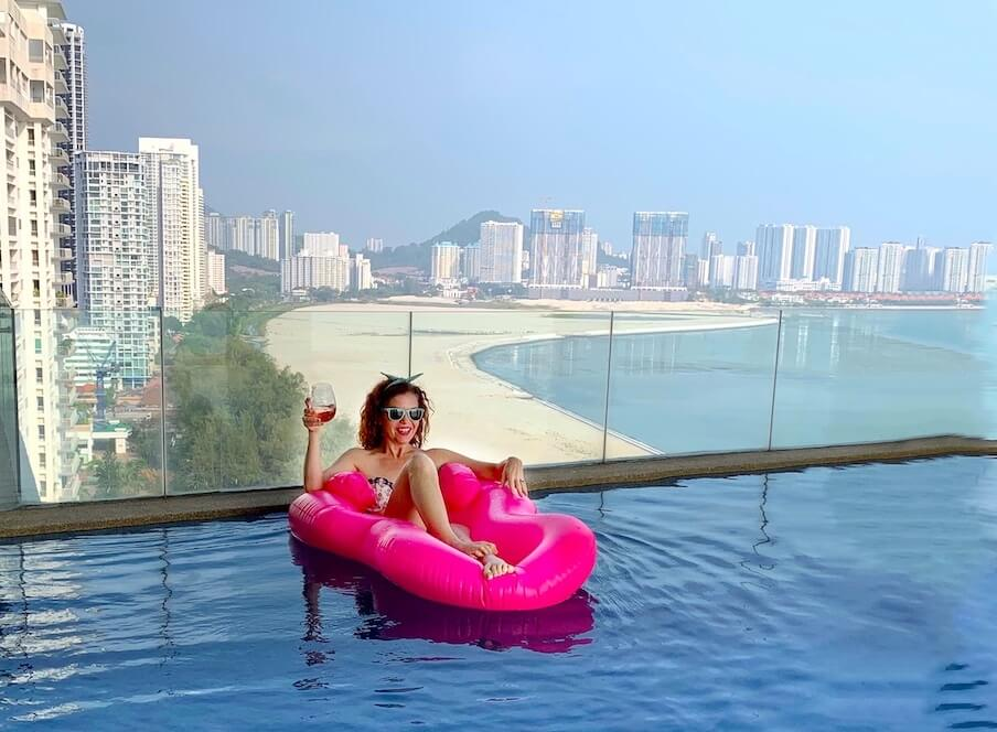 me in pool with pink floatie, penang in background