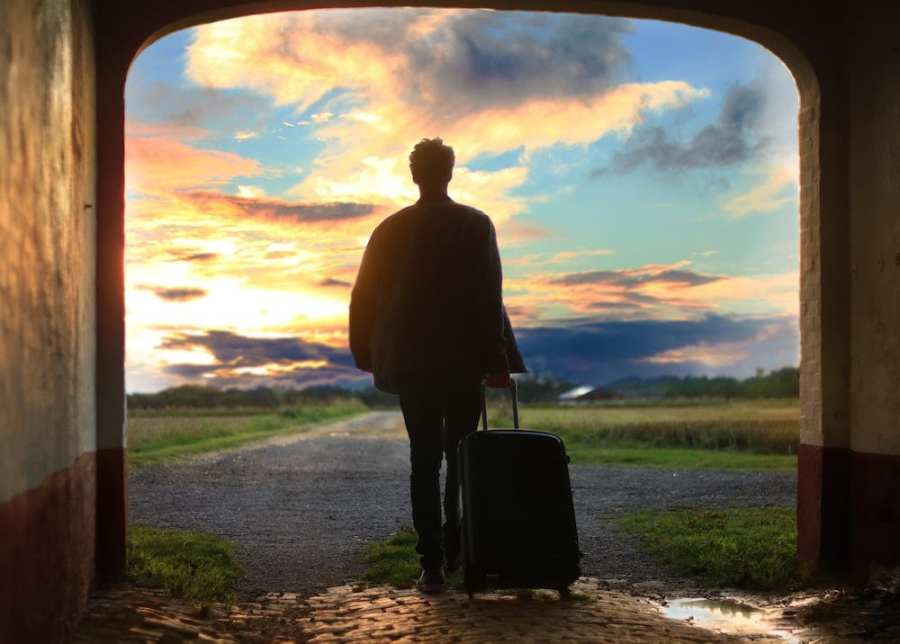 man walking with suitcase into sunset