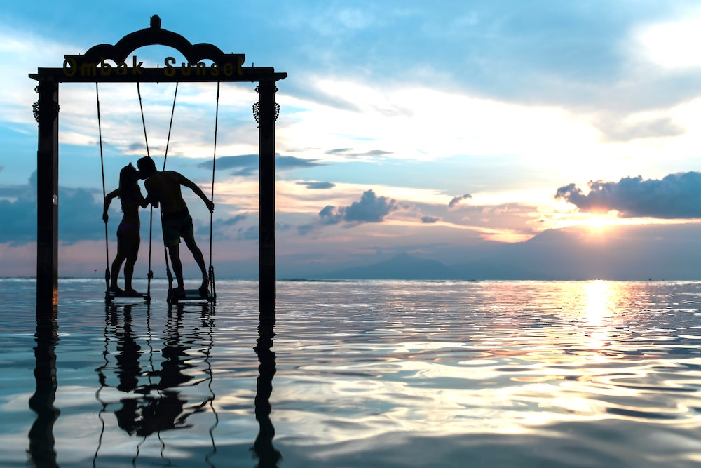 silhouette of couple kissing on swings over water