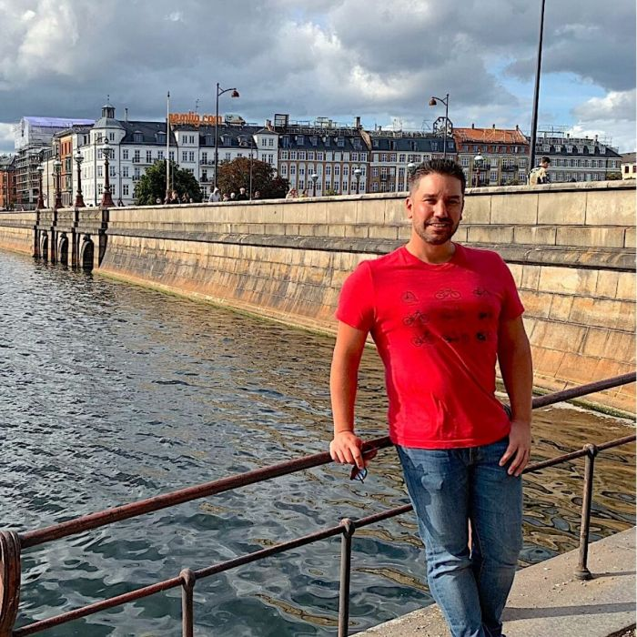 Guy in red shirt in front of water-expat in Denmark