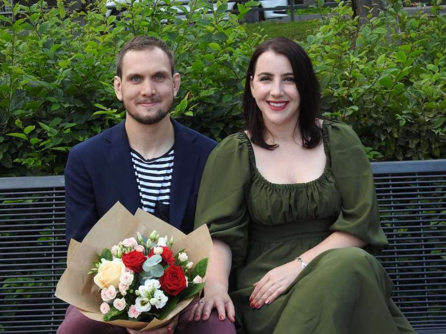 happy couple on a bench with flowers